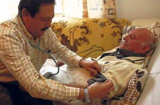 El enfermero Pancho Malvar ausculta a un paciente hospitalizado en su casa, en Cabral.  www.farodevigo.es. Foto: Joel Martínez